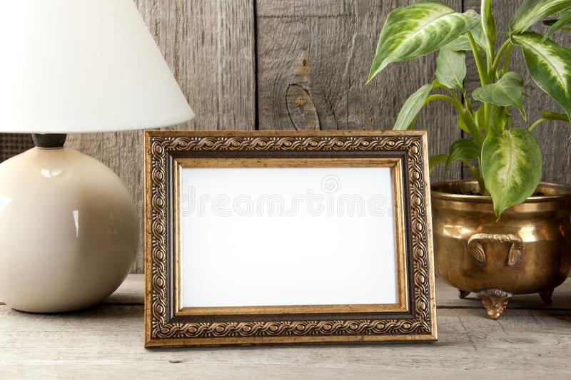 Empty brass picture frame on wooden background. stock image