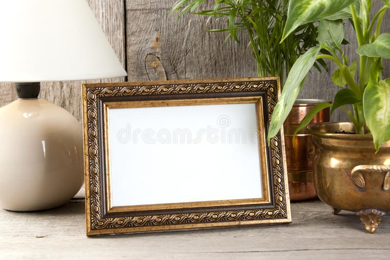 Empty brass picture frame on wooden background. stock photo