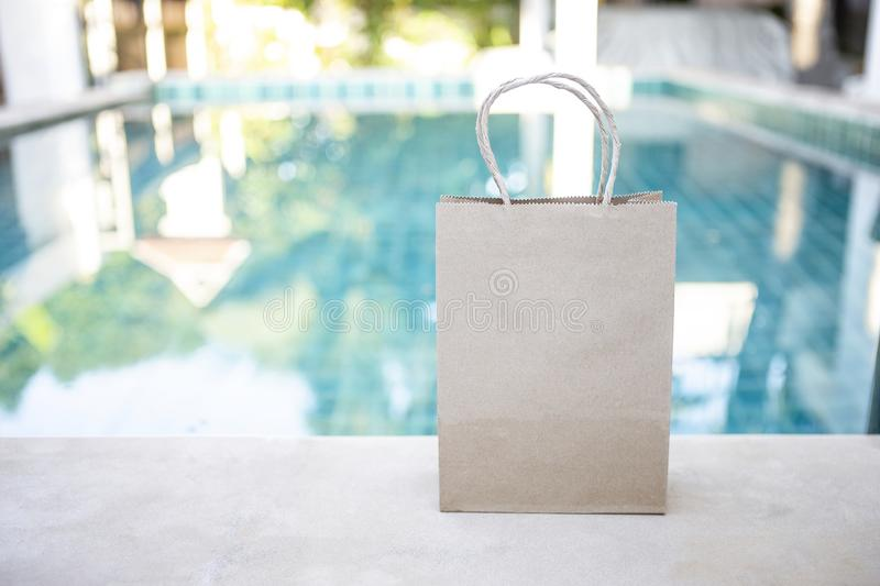 Empty brow paper shopping bag over blurred swimming pool background royalty free stock photography