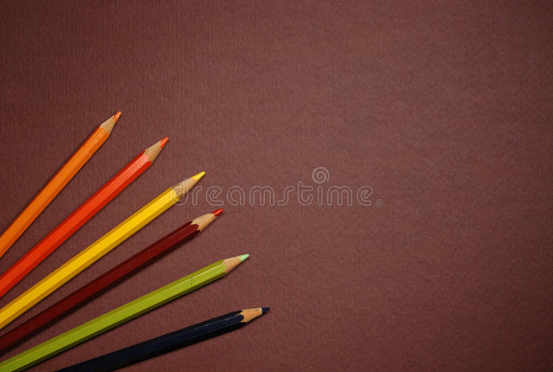 Empty brown cardboard and coloured pencils royalty free stock photography