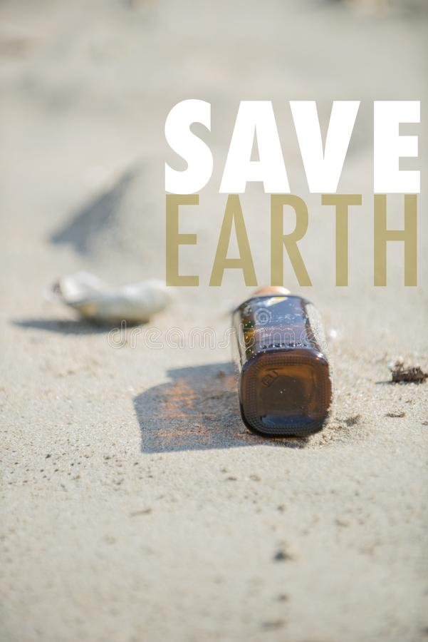 Empty brown clear bottle with cap left on the beach. Save Earth please!. Save Earth awareness on the Earth day. Empty brown clear bottle with cap left on the stock photo