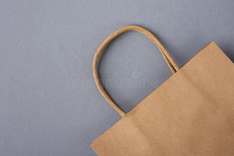 Empty Brown Craft Paper Bag on Gray Background. Sales Discount Shopping. Black Friday Cyber Monday. Christmas Gifts. Copy Space royalty free stock photography