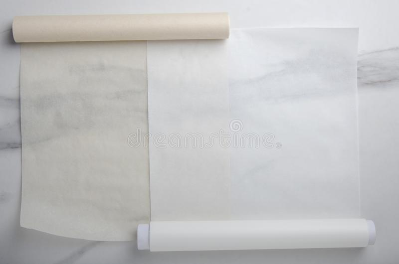 Two types of paper for baking on marble table royalty free stock image