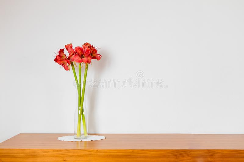 Empty brown wooden commode with three flowers on tablecloth. Red car carped, white wall royalty free stock image