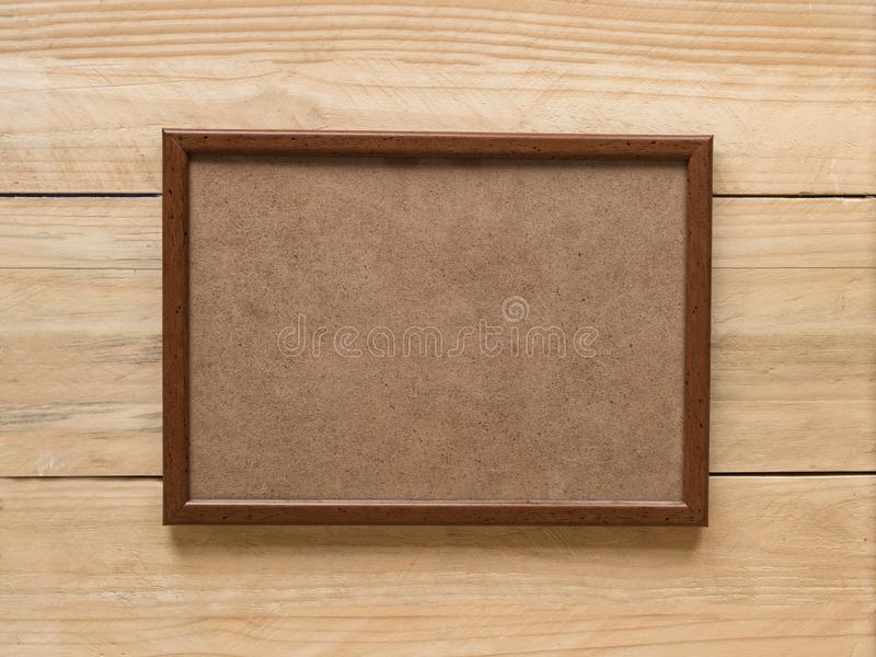 Empty brown wooden photo frame on light brown wooden wall. Mock up royalty free stock images