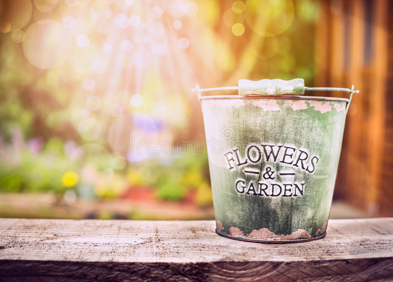 Empty bucket on old wooden table over summer or autumn garden background stock photography