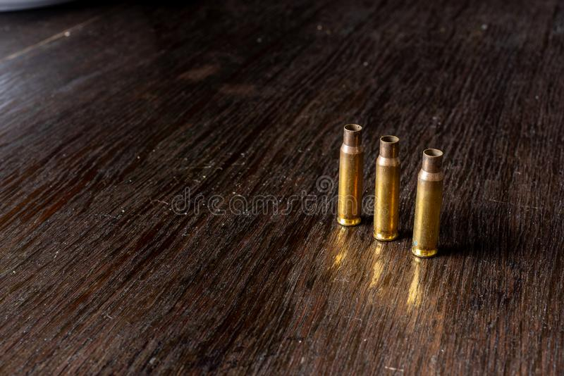 Empty bullet casings on a dark, wooden table royalty free stock images