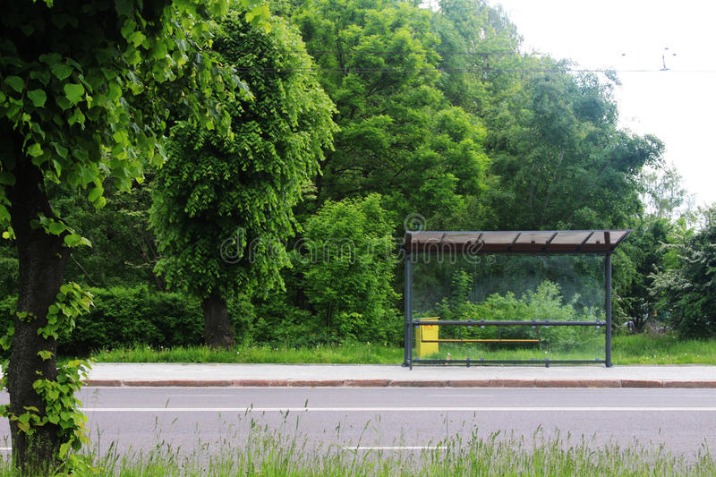 Empty bus stop in the green stock images