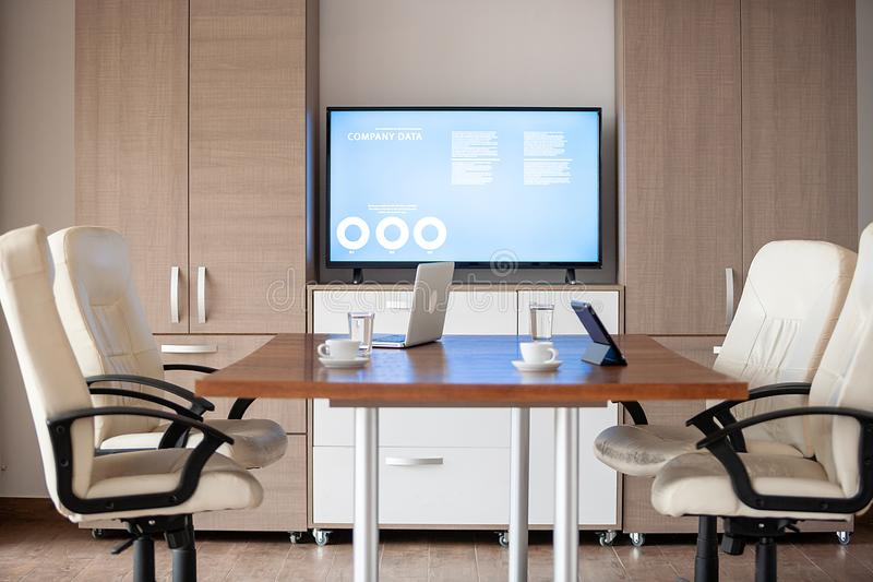 Empty business meeting conference room with graphs and diagrams on TV royalty free stock images