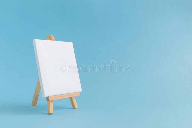 Empty canvas on easel. Easel for artists and blank canvas miniature on pastel blue background. Art minimal concept stock photo