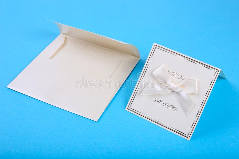 Empty card in blue envelope on blue background. Holiday and invitation mockup stock photos