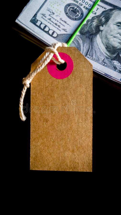 Empty cardboard tag for inscription black friday with american dollars on black background. Background, concept for the holiday. Black Friday - the royalty free stock photos