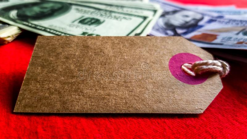 Empty cardboard tag for the inscription Black Friday with American dollars on a red background. Background, holiday concept. Black. Friday - International Day royalty free stock photo