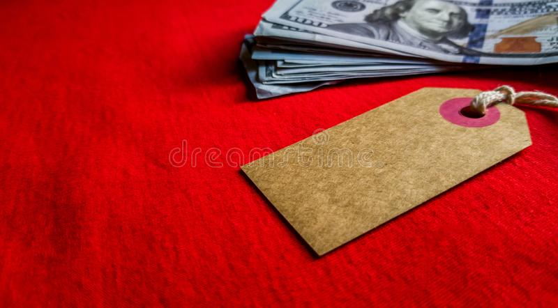 Empty cardboard tag for the inscription Black Friday with American dollars on a red background. Background, holiday concept. Black. Friday - International Day royalty free stock image