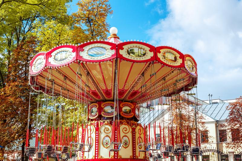 Empty Carousel Merry-Go-Round With Seats Suspended On Chains Wi. Thout People Waiting For Its Visitors. Attractions in the autumn, closing of attractions stock images