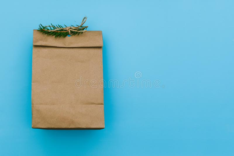 Empty carton pack with spruce branch. Brown package for gift or fast food. Paper bag for storing food on a blue royalty free stock image