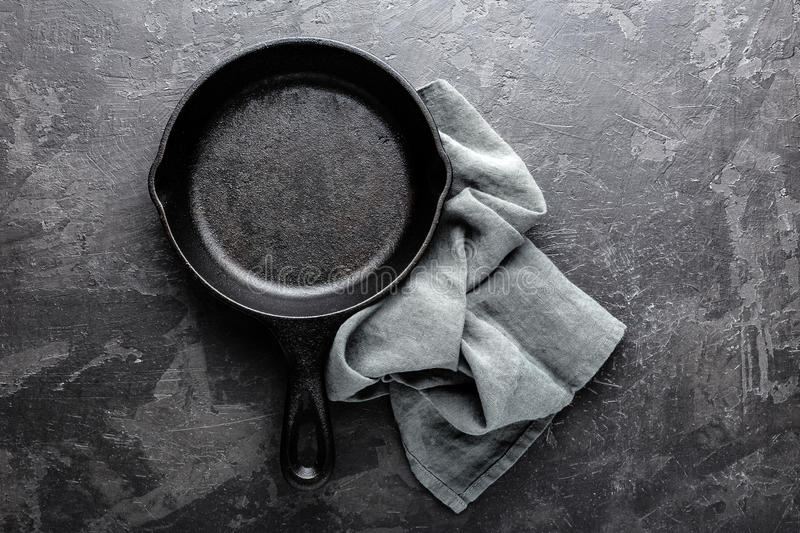 Empty cast iron frying pan on dark grey culinary background, view from above stock photography