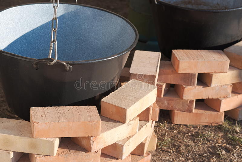 Empty Cauldrons and Bricks. Empty Clean Black Cauldrons and New Bricks Closeup royalty free stock photography