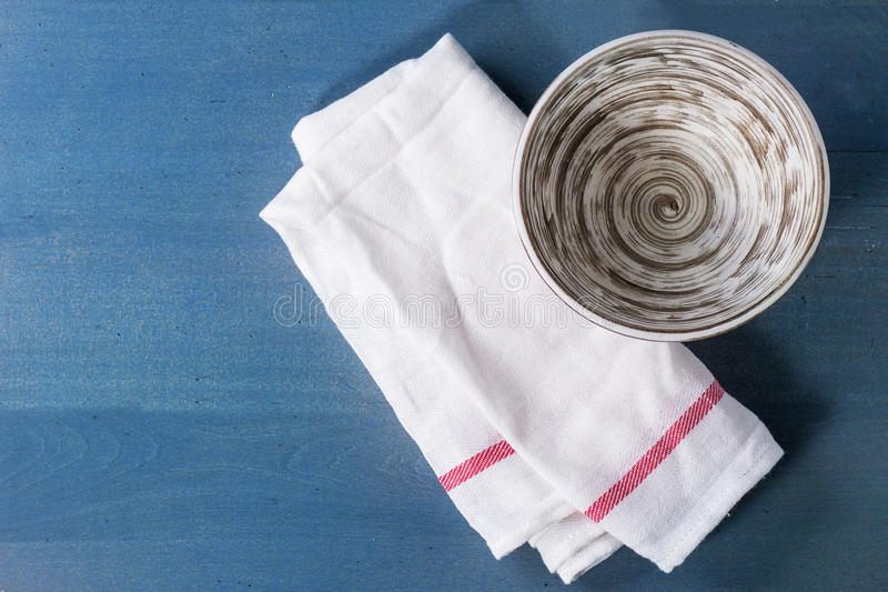 Empty ceramic bowl. On kitchen checkered towel over blue wooden surface. Top view royalty free stock image