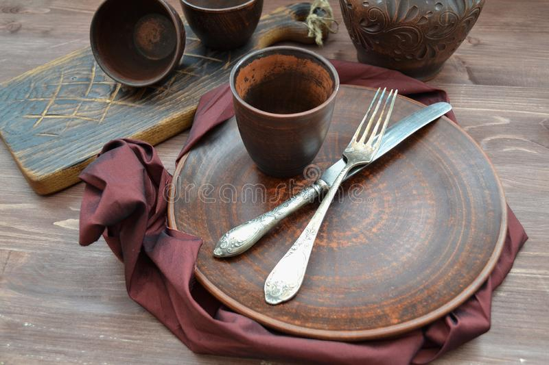 Empty ceramic dishware and wooden objets with grenadine napkin flat view. Empty ceramic dishware and wooden objets with grenadine napkin flat stock images