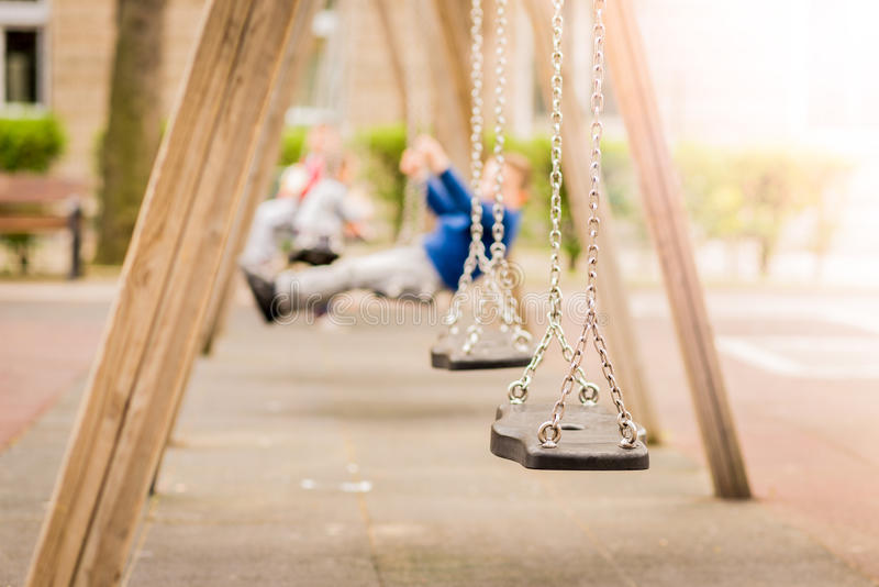 Empty chain swings in a playground. Blured background of swinging kids. Empty chain swings in a playground. Blured background of swinging kids on a sunny light stock photos