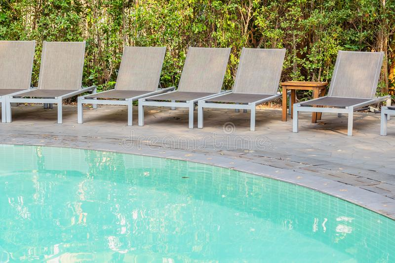 Empty chair around swimming pool in hotel resort. For travel leisure and vacation concept stock photos