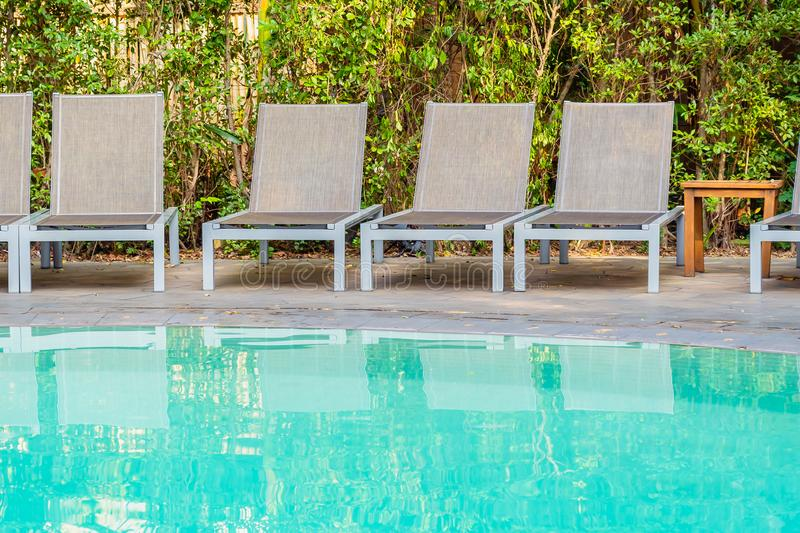 Empty chair around swimming pool in hotel resort. For travel leisure and vacation concept royalty free stock photos