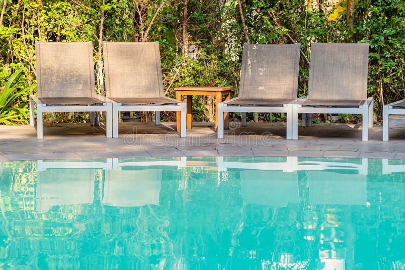 Empty chair around swimming pool in hotel resort. For travel leisure and vacation concept royalty free stock images