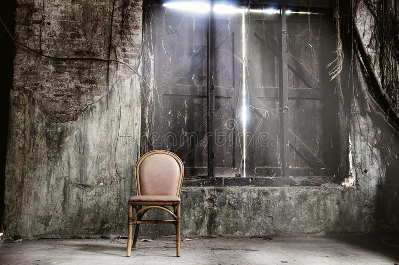 Empty chair and grungy wall stock photos