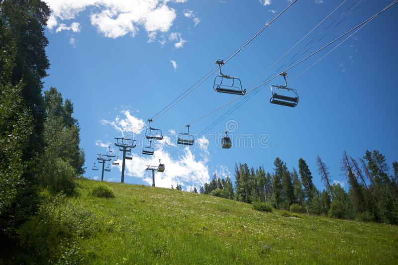 Empty chair lift in Vail, Colorado in summer. Viewed from the bottom of a lush green mountain slope with conifer forest against a blue sky stock photos