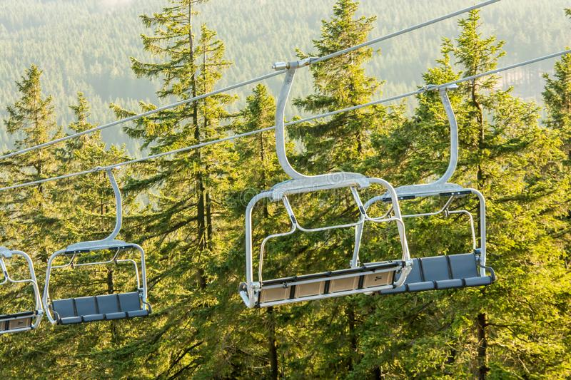 Empty chairlift with big gondolas in a forest area. Several empty large chairlifts go up and down in a wooded mountain area royalty free stock image