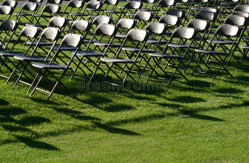 Empty Chairs. Rows of empty chairs outside on a green lawn. Corporate applications,events and more royalty free stock photos