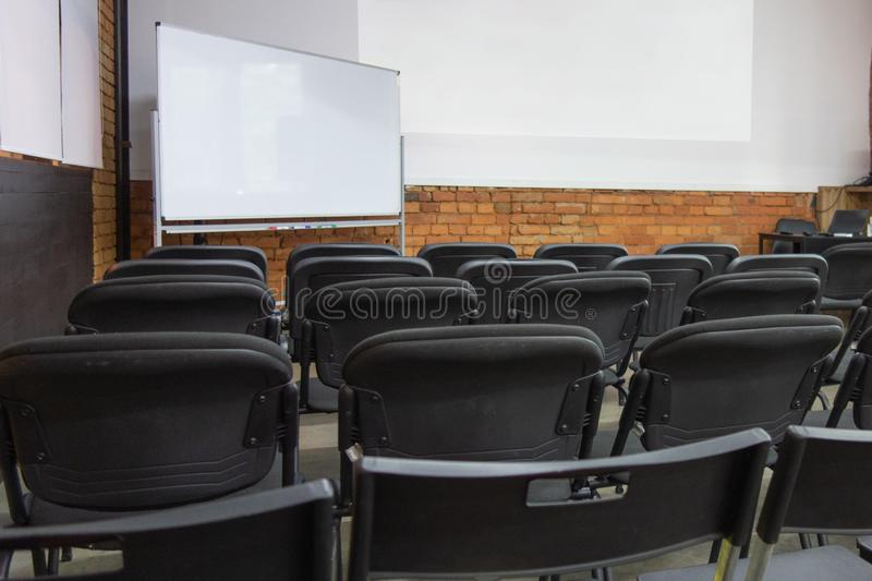 Empty chairs rows in front of white board and wall display before presentation or seminar. Classroom or conference hall before. Opening with no people. Backside stock photo