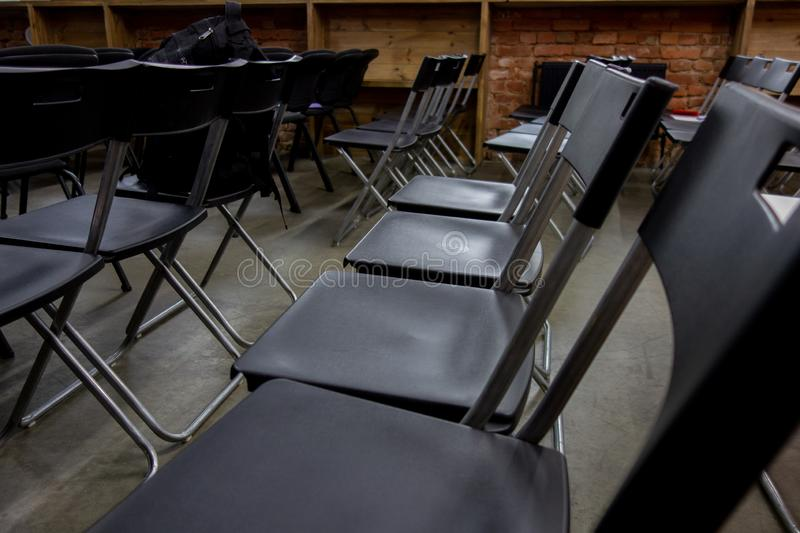 Empty chairs rows before presentation or seminar. Classroom or conference hall waiting opening with no people. Side view royalty free stock photos