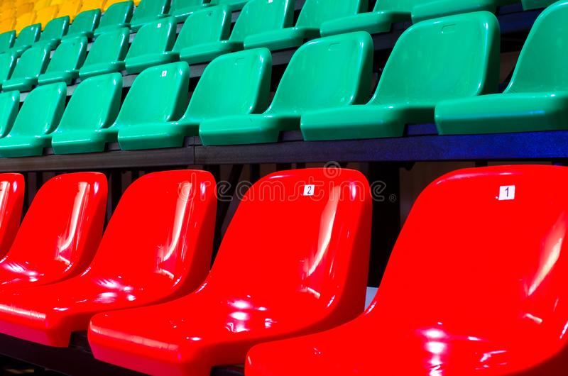 Empty chairs of stadium stands of green and red color. The auditorium in the sports complex with green and rede plastic seats. Places for spectators of a sports royalty free stock images