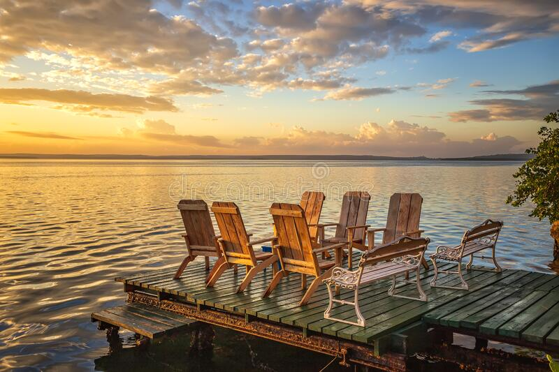 Amazing colorful sunrise in the sea. Empty chairs and table on a wooden pier at amazing colorful sunrise in the sea stock photography