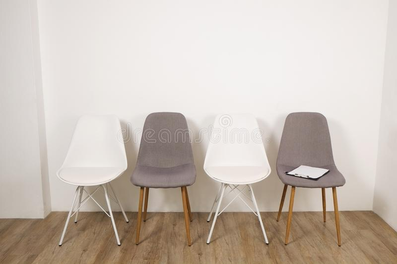 Empty chairs. Vacant job position concept. Minimlistic interior lofty room with elegant furniture pieces. Multiple loft style empty chairs standing in row on royalty free stock images