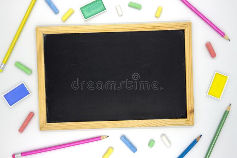 Empty chalkboard with art supplies on white background. Blackboard and colorful chalk flat lay photo. School supply banner template with text place. School stock image