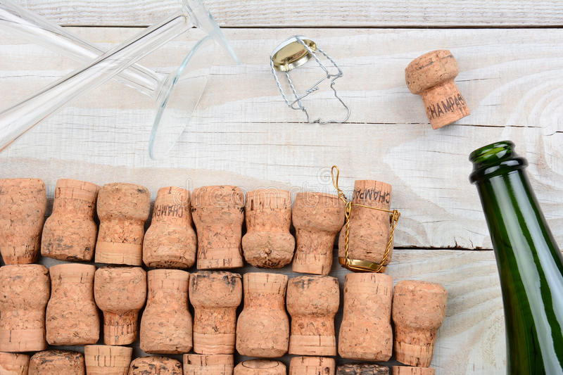 Empty Champagne Bottle and Corks. HIgh angle shot of a empty champagne bottle with corks and two flutes. Closeup on a rustic white wood table. Horizontal format stock photo