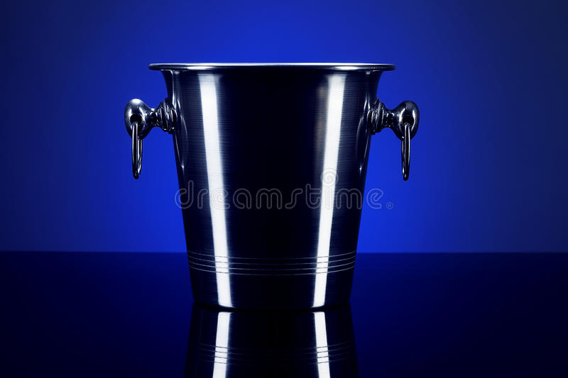 Empty champagne bucket. On a mirror with blue background royalty free stock photography
