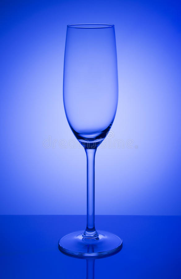 Empty champagne glass on a mirror with spot in blue background stock images
