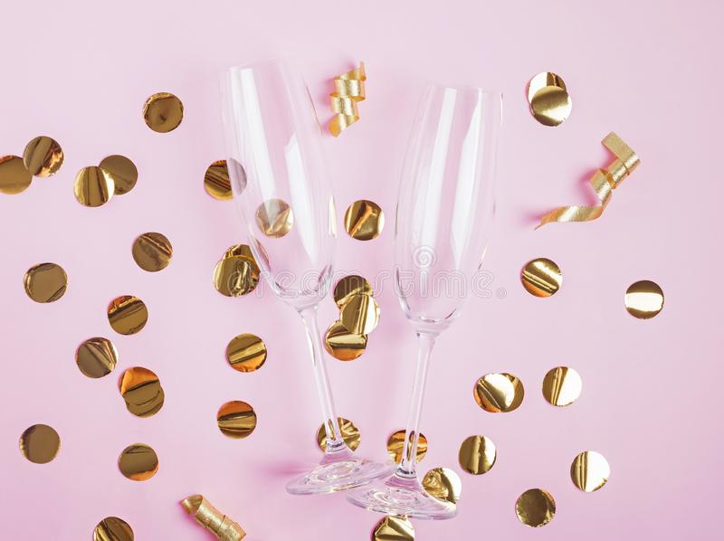 Empty champagne glasses lying on the golden confetti decor. Party accessories flat lay. Empty champagne glasses lying on the golden confetti decor royalty free stock photo