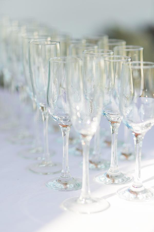Empty champagne glasses in a row on white tablecloth. royalty free stock photography