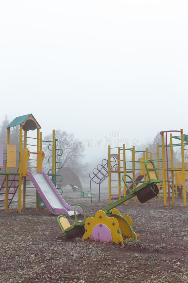 Empty children`s playground on a foggy autumn morning.  stock photo