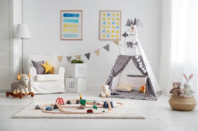 Empty children`s playroom with tent and toy railway stock photo