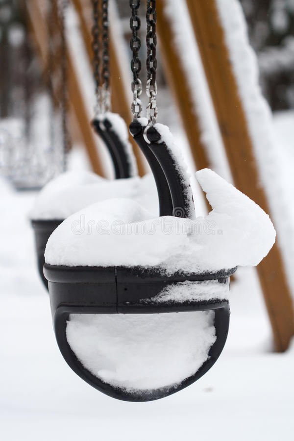 Empty children swing covered in snow. Vertical perspective view of black plastic child swings in the park covered in snow royalty free stock photo