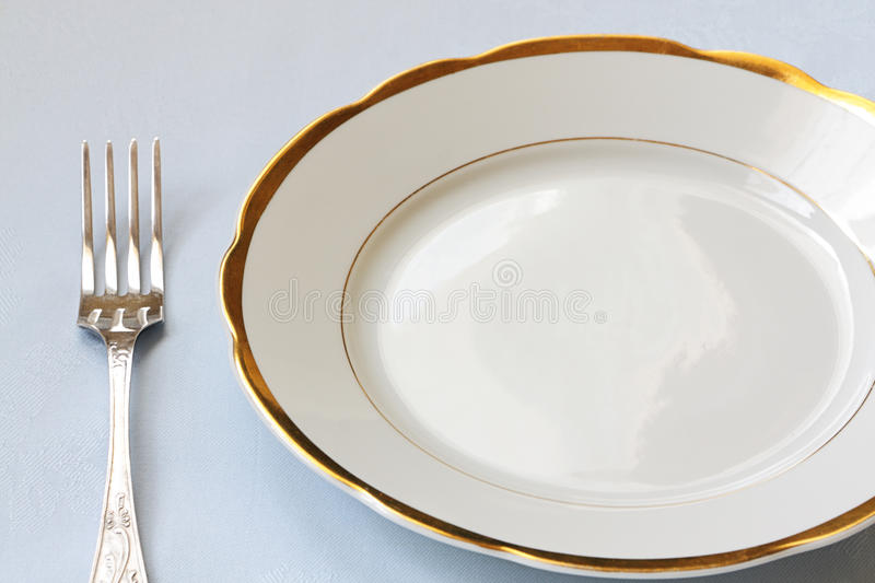 Empty china ware. And a dinner fork royalty free stock photos