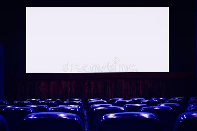Empty cinema auditorium with empty white screen. Empty rows of theater or movie seats. Blue toned royalty free stock images