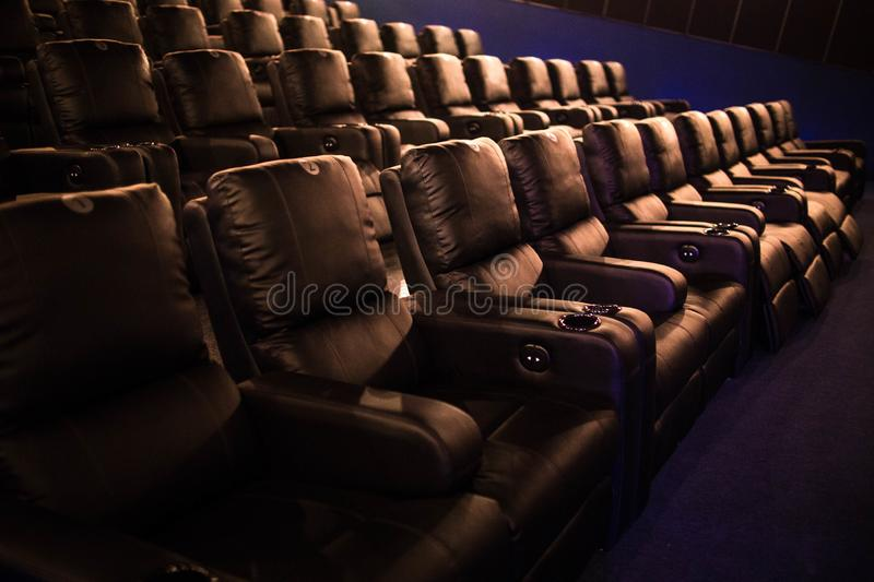 Empty cinema, cinema with soft chairs before the premiere of the film. There are no people in the cinema. Sliding automatic comfor. Table large leather chairs royalty free stock photography