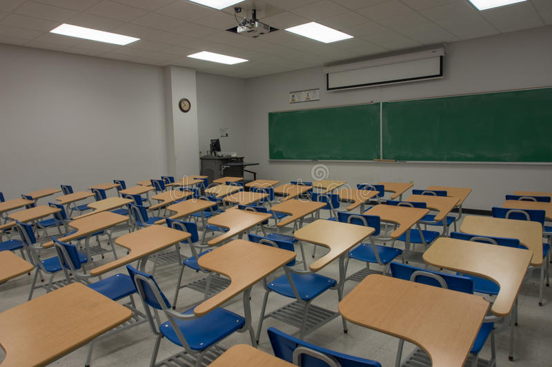 Empty Classroom. An empty classroom with blackboard and lecture chairs stock photo